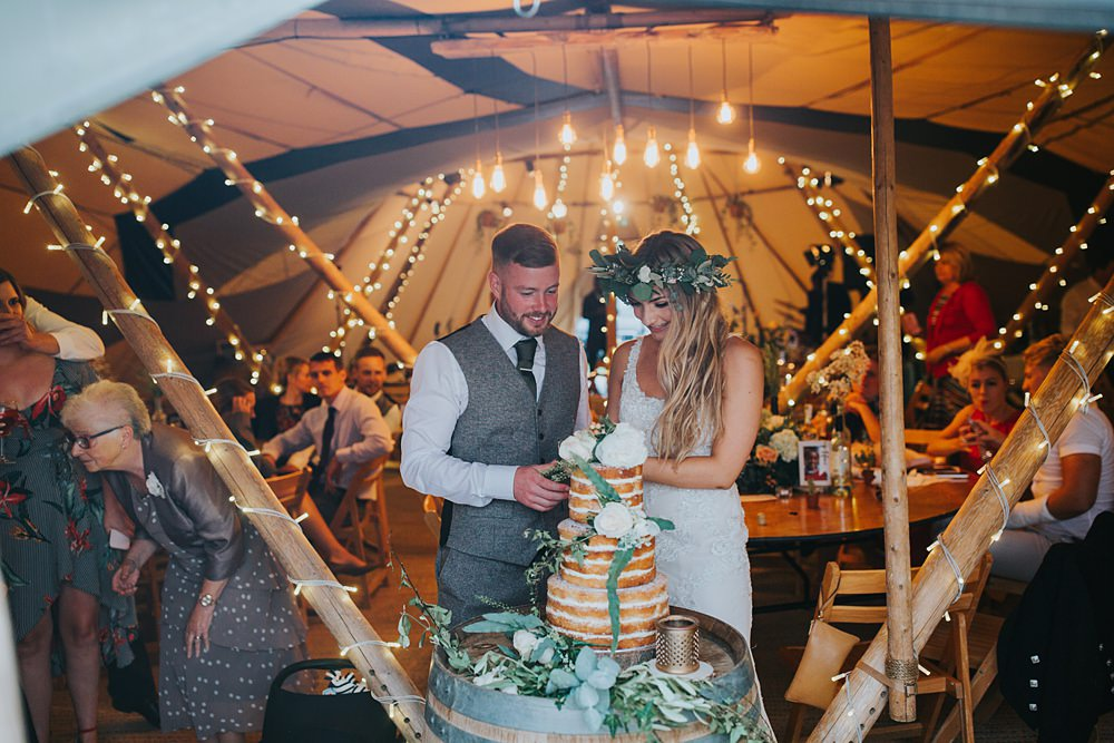 Bride and groom cutting cake at Tipi